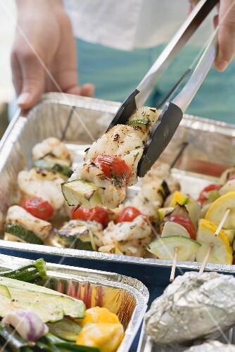 Woman holding fish and vegetable kebab in barbecue tongs