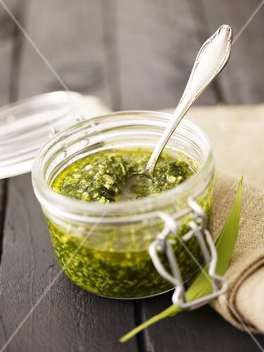 Ramsons (wild garlic) pesto in preserving jar with spoon