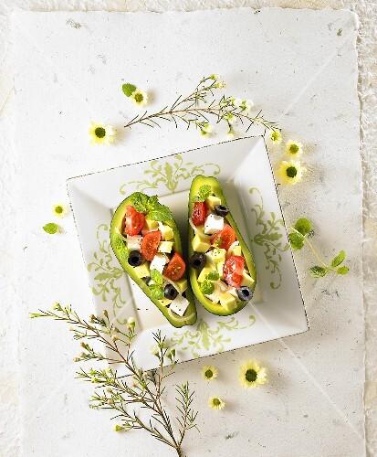 Avocado, tomato and cheese salad in two avocado halves