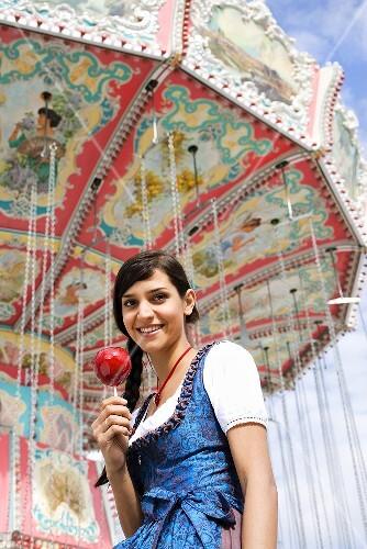 Woman in dirndl with toffee apple in front of swing ride (Oktoberfest)