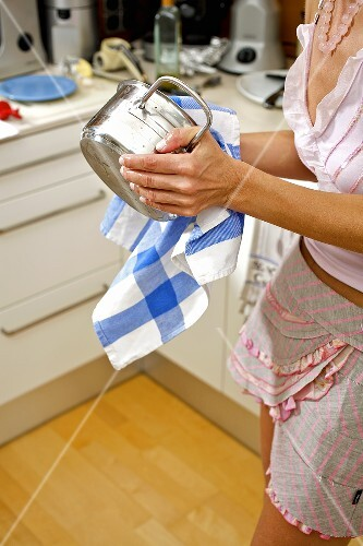 Woman drying a pan in a kitchen