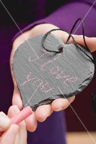 Hands holding chalk & a slate heart with the words I love you