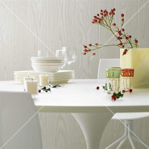 White tableware, glasses, candles, rose hips & holly on table