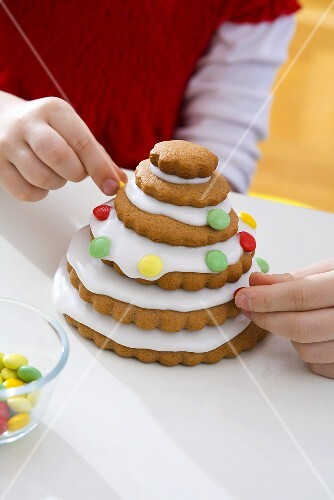 Children decorating Christmas tree made from biscuits