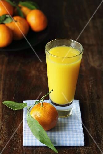 Glass of orange juice with fresh mandarin oranges