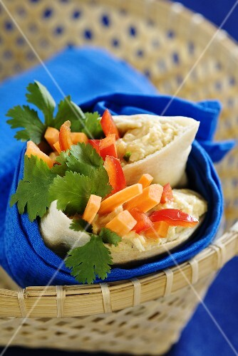 Pita bread filled with hummus, vegetables and coriander