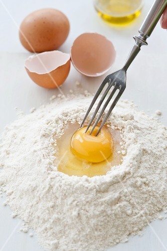 Hand pricking an eggs yolk on a mound of flour with a fork