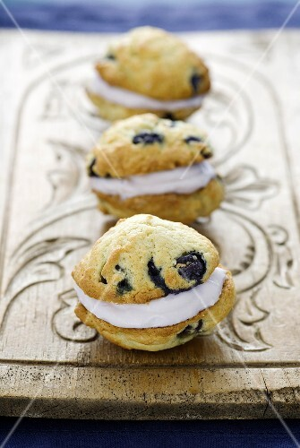 Three Whoopie Pies with blueberries on a wooden board