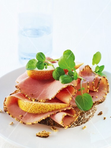 Bread topped with mustard ham, pears and water cress