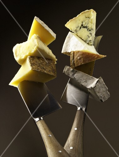 Various lumps of cheese on two knives