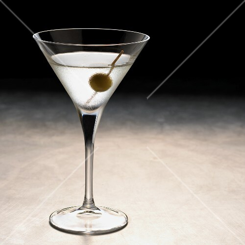 A glass of Martini with a green olive