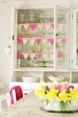 Cupboard full of glasses, narcissi on table