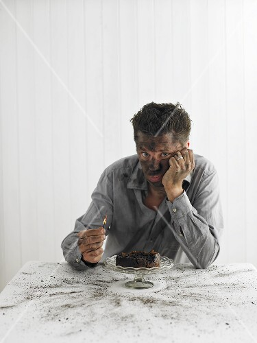Man with match sitting in front of exploded Christmas pudding