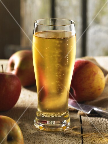 A glass of ice-cold cider with apples