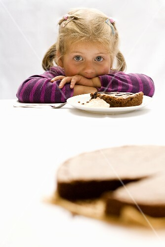 A little girl eating chocolate cake