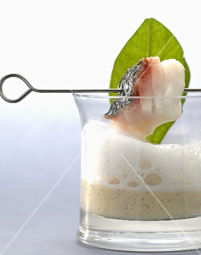 A piece of bass on a skewer above a glass of coconut and vanilla puree with milk foam