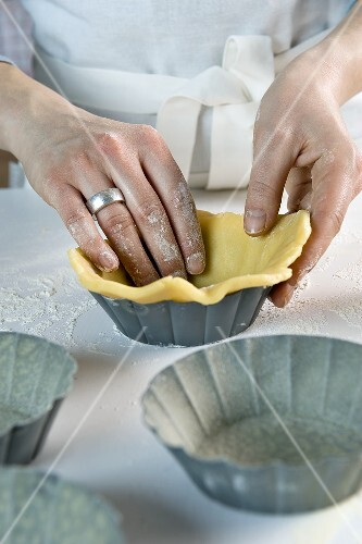 Shortcrust pastry being placed into baking tins