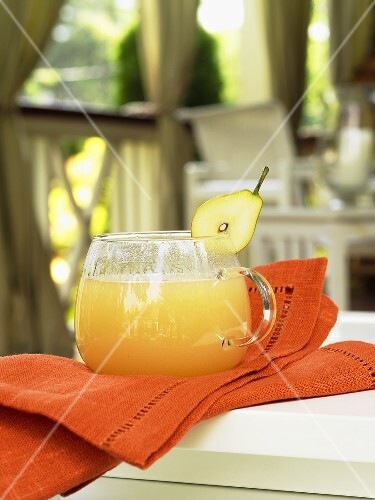 Pear punch in a glass cup on an orange napkin