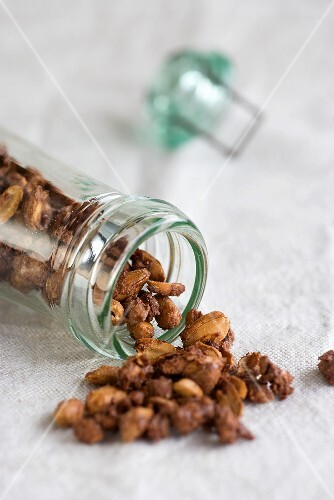 Roasted peanuts spilling out of a jar