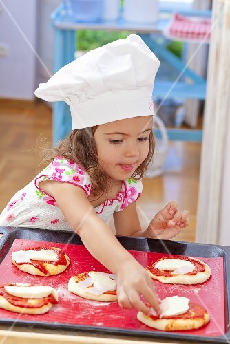 A little girl placing toppings on a pizza