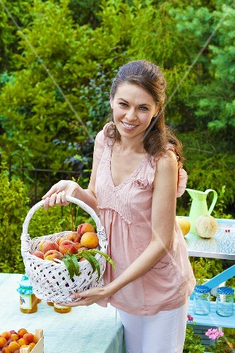 Young woman showing a basket with fresh peaches