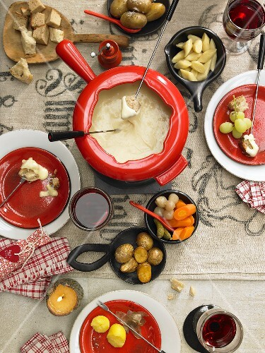 Swiss cheese fondue with potatoes, bread and vegetables (seen from above)