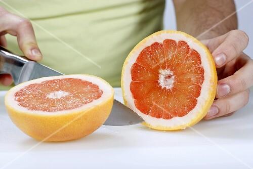 A man cutting a grapefruit in half