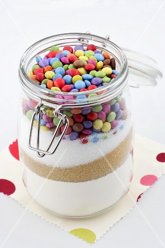 A jar of flour, brown sugar, white sugar and colourful chocolate beans