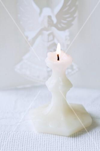 Weisse Kerze, dahinter Engel aus Papier gefaltet