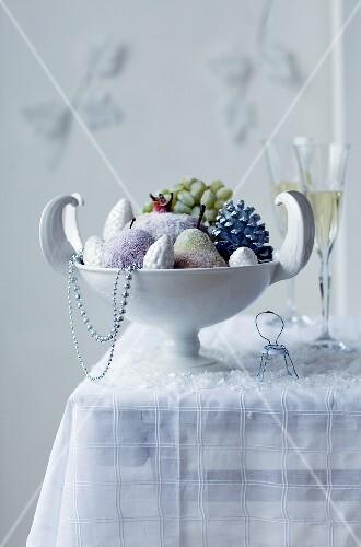 weiße Schale mit gezuckerten Früchten & Zapfen auf Tisch