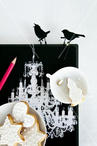 Mürbteigplätzchen mit weissem Zuckerguss und schwarze Deko-Vögel