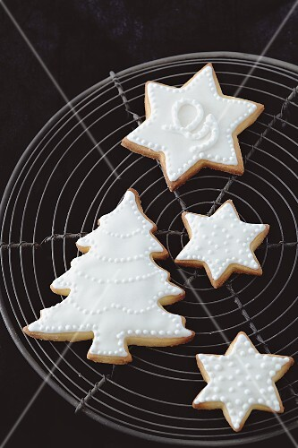 Shortbread biscuits with white icing (a Christmas tree and stars) on a wire rack