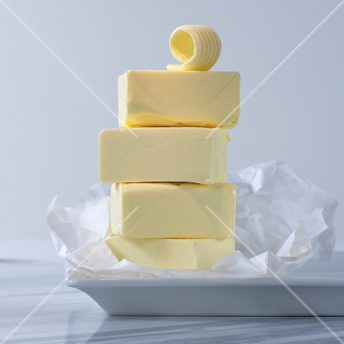 Sticks of butter, stacked, with butter flakes