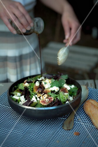 Pouring vinaigrette on green salad with roasted figs and marinated sheep's cheese