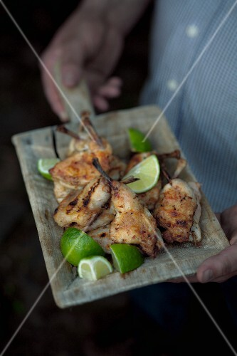 A man serving barbecued spring chicken with limes