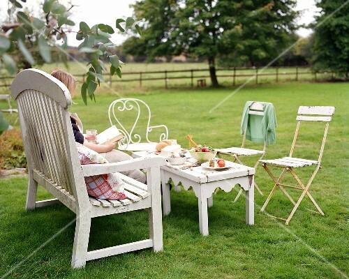 Snacks on garden table, a woman reading a book