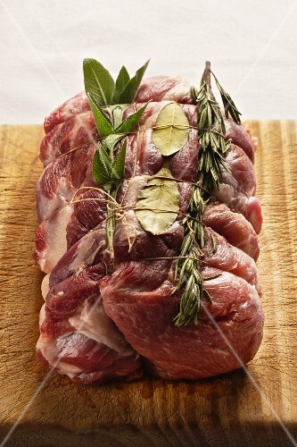 Raw rolled roast pork with rosemary, bay leaf and sage