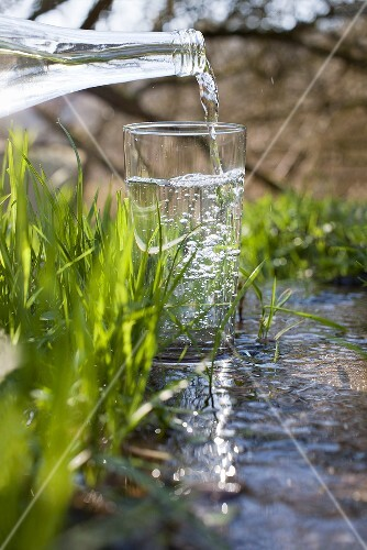 Water being poured into a glass standing in a stream