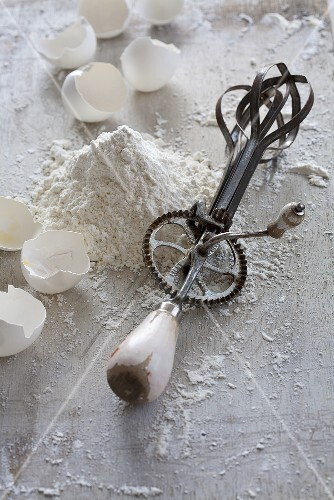 An old fashioned hand whisk with flour and egg shells