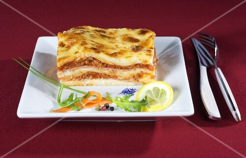 A slice of lasagne with a side salad and lemon