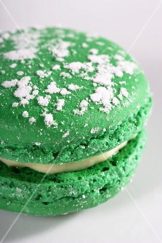 A green macaroon with lemon cream and icing sugar