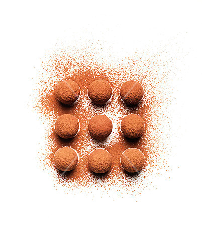 Truffle and cocoa powder composition on a white background