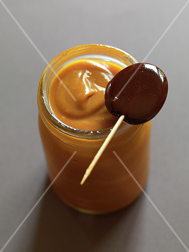 Pot of milk jam and a caramel lollypop