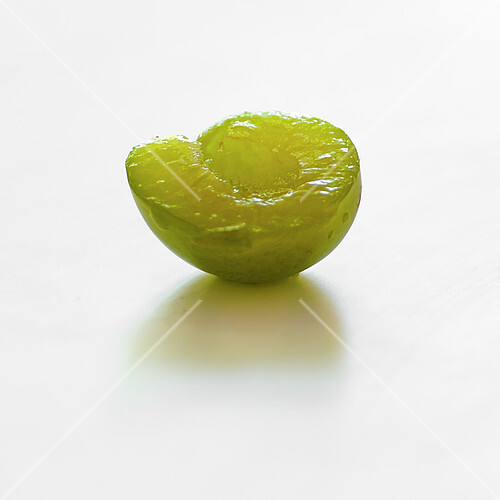 Half a greengage plum on a white background