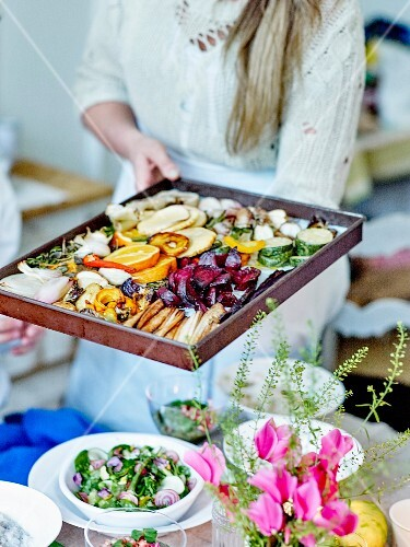 Woman presenting a dish of oven-baked vegetables