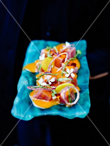 Red tuna tartare with red onions, yellow carrots, flowers and samphire