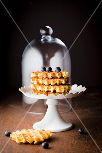 Pile of waffles Liégeoises, blueberries and a glass dome