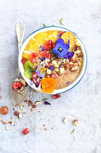 Banana, pineapple, kumquat, kiwi, pomegranate seed and hazelnut smoothie bowl