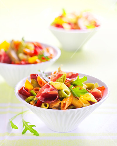 Multicolored penne with raw ham and rocket lettuce