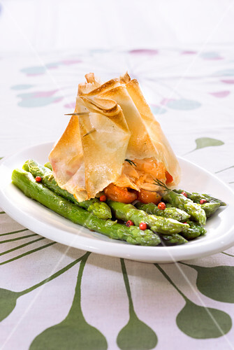 Pan-fried green asparagus with pink pepper and preserved cherry tomatoes, salmon crisp filo pastry purse